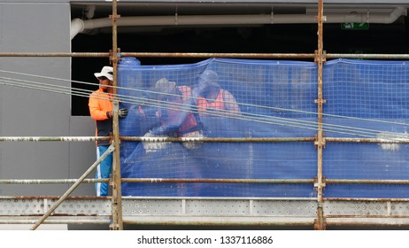 Gosford, New South Wales, Australia - March 6, 2019: Workmen close up, dismantling scaffolding and removing safety netting on new home units building site at 47 Beane St. Construction update 208.