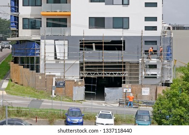 Gosford, New South Wales, Australia - March 6, 2019: Workmen dismantling scaffolding and removing safety netting on new home units building site at 47 Beane St. Construction update 209.