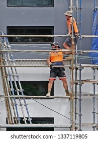 Gosford, New South Wales, Australia - March 6, 2019: Workmen close up, dismantling scaffolding and removing safety netting on new home units building site at 47 Beane St. Construction update 210.