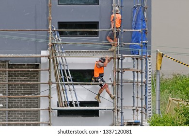 Gosford, New South Wales, Australia - March 6, 2019: Workmen close up, dismantling scaffolding and removing safety netting on new home units building site at 47 Beane St. Construction update 211.