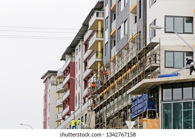 Gosford, New South Wales, Australia - March 18, 2019: Workmen close up, dismantling scaffolding and removing safety netting on new home units building site at 47 Beane St. Construction update