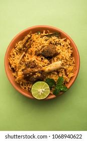 Gosht or Lamb Biryani prepared in Basmati Rice served with Yogurt dip in terracotta bowl. Selective focus