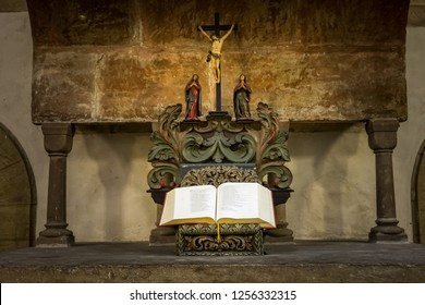 Goslar, Germany, December 11., 2018: Carved Jesus figure on the cross with praying and mourning women behind an open Bible on a worn altar made of heavy compact stone