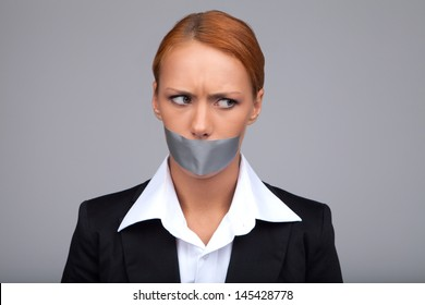 Gossip businesswoman. Portrait of beautiful young businesswoman with her mouth covered with an adhesive tape standing isolated on gray