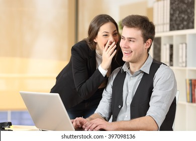 Gossip businesswoman telling secrets to the ear of a businessman sitting on a desktop at office