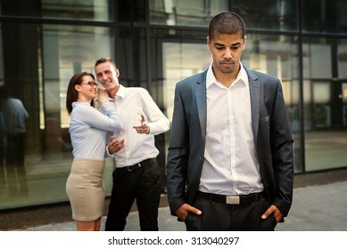 Gossip colleagues in front of their office, handsome businessman portrait and gossip out of focus in background.