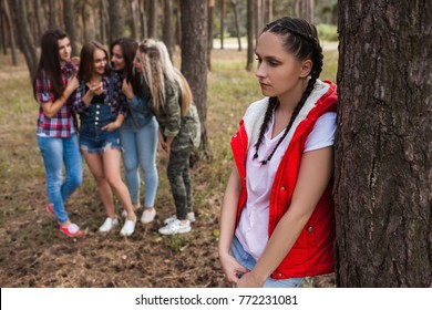 Gossip upset girl forest friendship strife concept. Female rivalry and discussion behind the back. Betrayal and sadness.