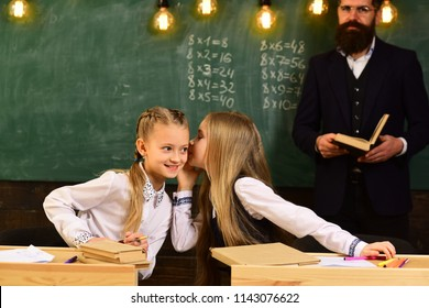 gossip whispering, little girls whispering gossip at school lesson. gossip whispering of two girls friends. gossip whispering concept. gossiping