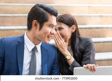 Gossip in the workplace. Business Woman whispering to colleague during work together. Man face is surprised about rumour.
