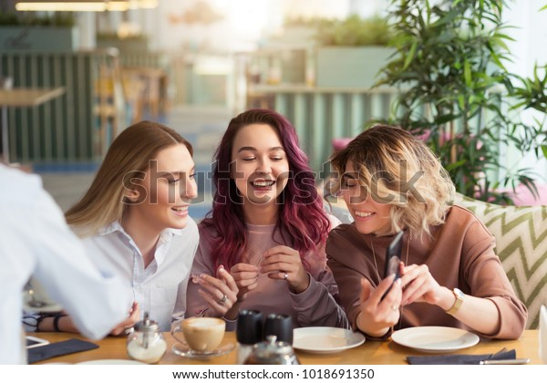 Gossipgirls, freindship concept. Female friends with tea and coffee speaking in cafe, gossip and news. Smiling women laughing, talking and smiling together in coffee shop