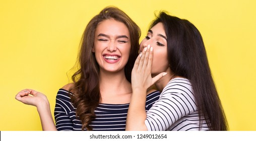 Gossiping is fun for women. Two excited girls telling each other secret, bright yellow background