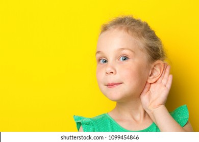 Gossip,rumors, whisper, hearing concept. Young blonde Woman putting hand ear to hear better. Studio shot on yellow background.