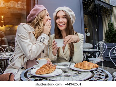 Gossips with best friend. Horizontal shot of beautiful woman whispering to her friend's ear while drinking coffee in french vintage cafe. Women friends gossiping during coffee time. French style women