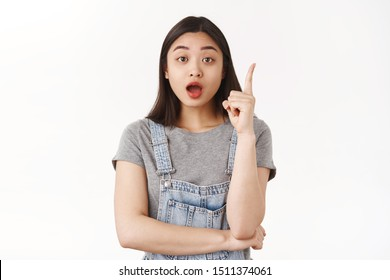 Got excellent idea. Cute creative asian female coworker explain plan raise index finger eureka gesture introduce solution suggest how solve situation speaking passionately own invention