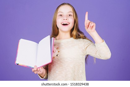 Got great idea. Happy little girl holding open idea book and keeping finger raised. Smiling small child having an idea. Idea came into her head, copy space.