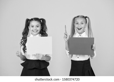 Got idea. Small cute kids smiling of genius idea. Happy girls holding paper sheets for writing idea on yellow background. Little children with empty paper for creative idea, copy space.