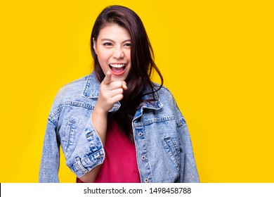 I got you. Attractive beautiful asian woman pointing finger to special people or customers. Pretty woman wear denim jacket with smile face. She want telling winter season is coming, has special offers