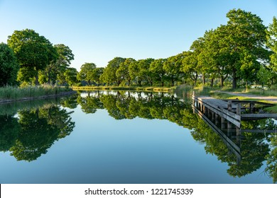 The Gota canal in Sweden, dead calm in evening sunlight with a row of green trees along the riverbank reflecting or mirroring in the still peaceful water