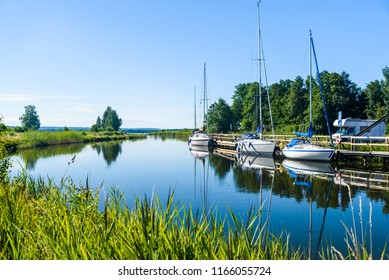 The Gota canal at Tatorp, Sweden, on a sunny summer day. Sailboats moored by the pier.