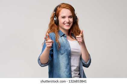 Gotcha! Attractive redhead girl in headphones pointing her index fingers at camera cheerfully, gray background