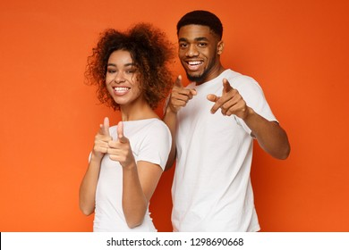 Gotcha! Cheerful young african-american man and woman pointing fingers at camera, orange studio background