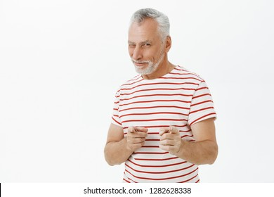 Gotcha. Portrait of charismatic and optimistic energized male mature pensioner in striped t-shirt pointing with index fingers at camera smiling daring and excited, greeting or inviting friends
