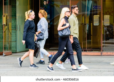 Goteborg, Sweden - July 25, 2016: Unknown couple walking along the sidewalk holding hands. Real people in everyday life.