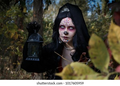 Goth Dresed girl walk in forest with lamp