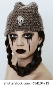 goth girl in hat with skull posing on white background