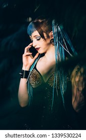 Goth girl talking on the phone in tropical garden