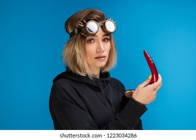 Goth girl wearing steam punk glasses and dark hoodie is looking confused at a red chilli pepper. Longsleeve goth girl fashion