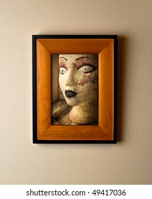 Goth grunge mannequin head image in a beautiful wooden frame. Ironic or funny home decor element.