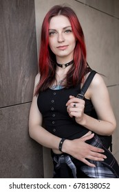 Goth punk beautiful girl with red hair walks in the city
