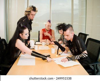Goth / Punk Business Team. Group of people in alternative styles arguing around a boardroom table.