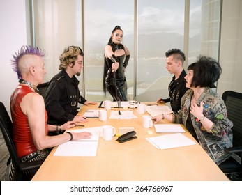 Goth / Punk Business Team. Group of people in alternative styles arguing around a boardroom table with a woman wearing a PVC dress directing the meeting with a riding crop.