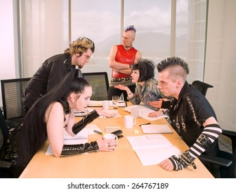 Goth / Punk Business Team. Group of people in alternative styles arguing around a boardroom table. Older man with a mohawk at the head of the table is unimpressed.