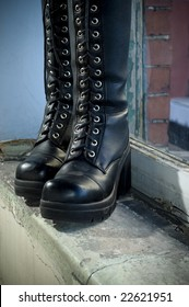 Goth punk knee-high fashion boots standing on old window sill.