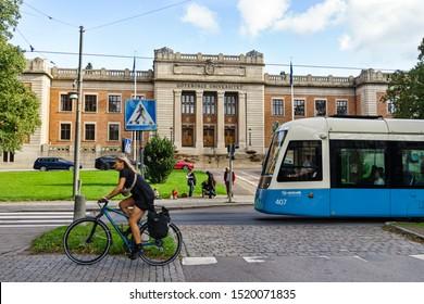 Gothenburg, Sweden - 7th September, 2019 : Public transport Tram and bike passing in front of University of Gothenburg, It is main building of University