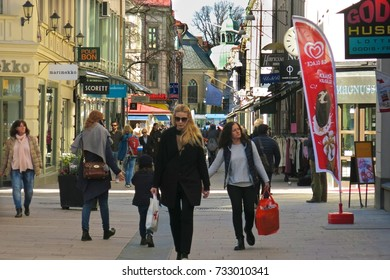 GOTHENBURG, SWEDEN – APRIL 11, 2016: Shoppers with shopping bags on Korsgaten, a busy shopping street in Gothenburg, Sweden, on a sunny day.