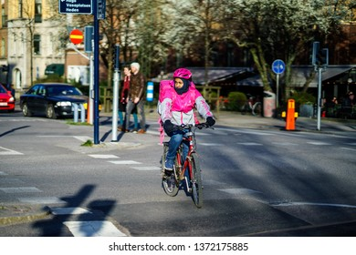 Gothenburg, Sweden - April 11, 2019: Foodora driver is riding to food of customer by bike in Gothenburg, Sweden