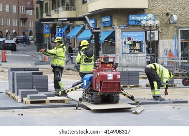 GOTHENBURG, SWEDEN - APRIL 21: Construction workers renews the main street of Gothenburg, Avenyn with new bricks on April 21, 2016 in Gothenburg.
