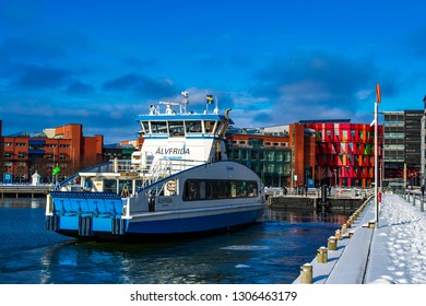 Gothenburg / Sweden - Feb 03 2019: A white and blue passenger ferry (Alvsnabben) at the quay of Lindholmen in the winter. University of Gothenburg and Chalmers campus buildings in the background.