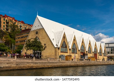 GOTHENBURG, SWEDEN - JULY 17, 2019: Low angle sea view of the church like famous historic Feskekorka fish market building. Incidental people in the foreground in Gothenburg Sweden July 17, 2019.
