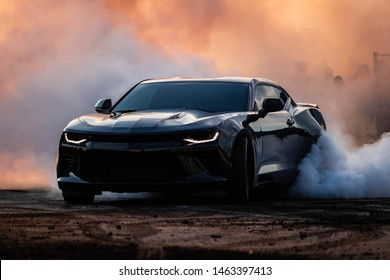 Gothenburg, Sweden - July 27, 2019: Muscle car doing a burnout with a crowd in the background at a car show.