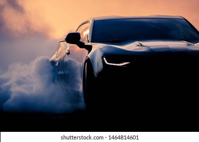 Gothenburg, Sweden - July 27, 2019: Black Camaro doing a burnout at a car show, dramatic edit