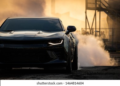 Gothenburg, Sweden - July 27, 2019: Black Camaro doing a burnout at a car show, structures in the background. Sunset