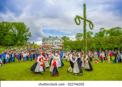 GOTHENBURG, SWEDEN - JUNE 19, 2015: Unknown dancers in traditional swedish dress dancing around the maypole for Midsummer celebration in Gunnebo Castle