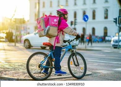 Gothenburg, Sweden - March 23, 2019: Foodora delivery man waiting on red light while making his delivery