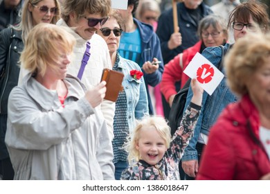 GOTHENBURG, SWEDEN - MAY 1, 2019: May 1 protest march in Gothenburg 2019, labor day. Happy young girl with a smile on her face waving with left party (vansterpartiet) symbol in the parade.