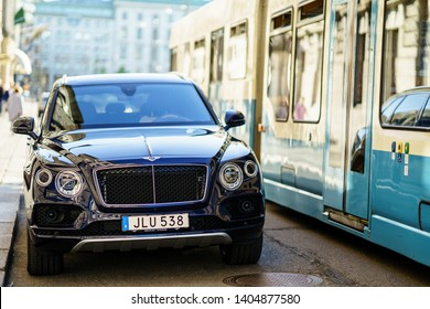Gothenburg, Sweden - May 16th, 2019 : Bentley Bentayga parked near by river and public tram passing on street, Gothenburg